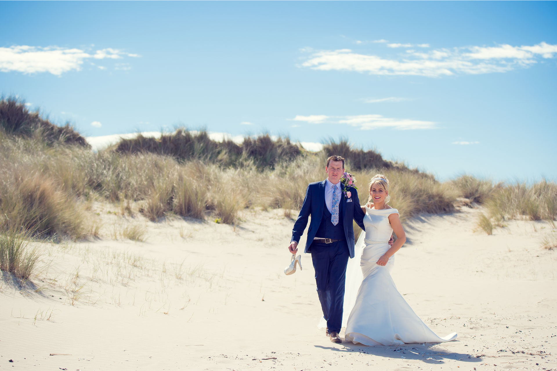 Photo of Noeleen and Cahal on their wedding day as they take a stroll on Benone Beach, Downhill, Coleraine, Co. Derry / Londonderry, Northern Ireland.
